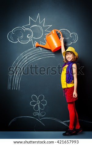 Joyful pretty girl in colorful clothes watering flowers drawn on a blackboard. Happy childhood. - stock photo