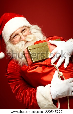 Joyful Santa Claus with big red sack full of gifts looking at camera - stock photo