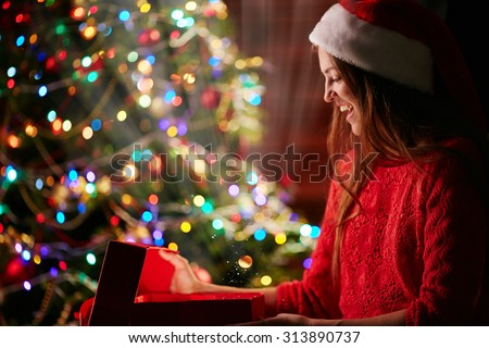 Joyful Santa opening magic box with Christmas gift - stock photo