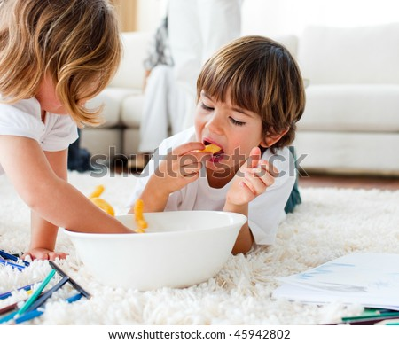 Joyful siblings eating chips and drawing lying on the floor - stock photo