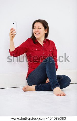 Joyful smiling woman taking selfie, sitting on white floor against white wall - stock photo