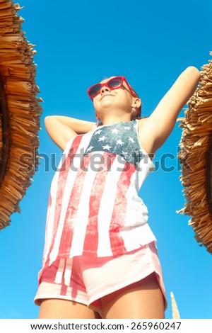Joyful smiling young girl having sunbath in tropical resort. Summertime outdoors. - stock photo