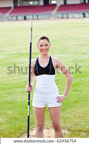 Joyful sporty woman holding a javelin standing in a stadium and smiling at the camera - stock photo