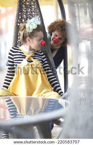Joyful street clowns performance; funny cafe visitors - stock photo