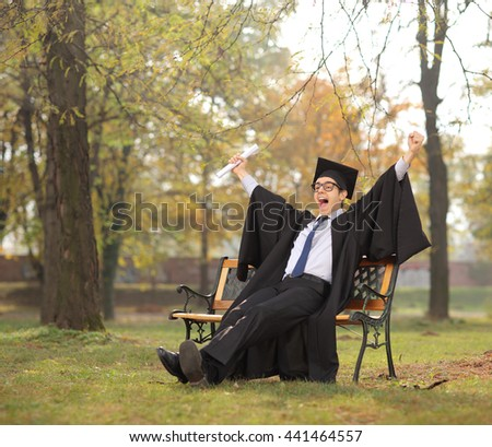 Joyful student celebrating his graduation seated on a bench in a park shot with tilt and shift lens - stock photo