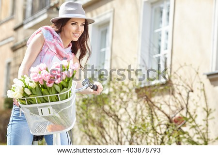 Joyful stylish woman in gray hat  on a bicycle with spring flowers on a background of the city - stock photo