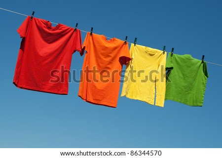 Joyful summer laundry. Colorful t-shirts on a laundry line and blue sky. - stock photo
