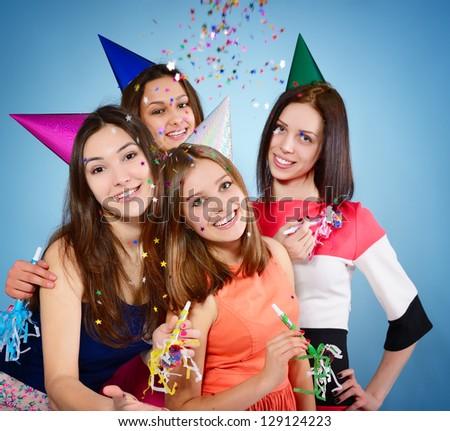 Joyful teen girls have fun on birthday party, over blue - stock photo