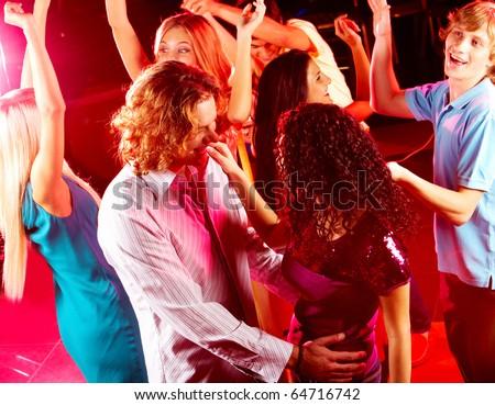 Joyful teens dancing in night club at party - stock photo