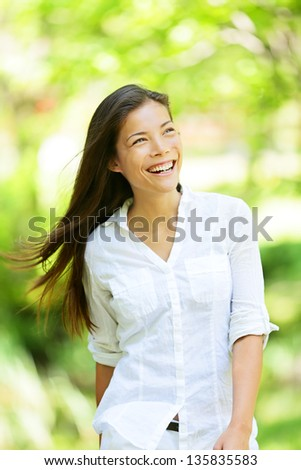 Joyful vivacious woman in a spring or summer park beaming a broad smile as she walks along rejoicing in the freshness of nature and the warm glow of the sunlight through the leaves of the green trees - stock photo