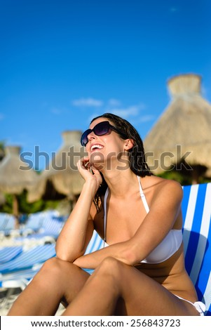 Joyful woman at tropical resort caribbean beach looking up to the blue sky. Summertime vacation tourism and travel concept. Beautiful brunette sunbathing and relaxing at Mayan Riviera, Mexico. - stock photo