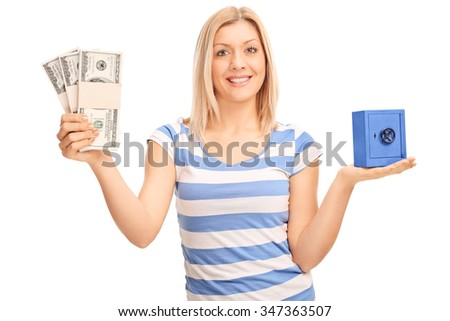 Joyful woman holding a few stacks of money and a small blue safe isolated on white background  - stock photo