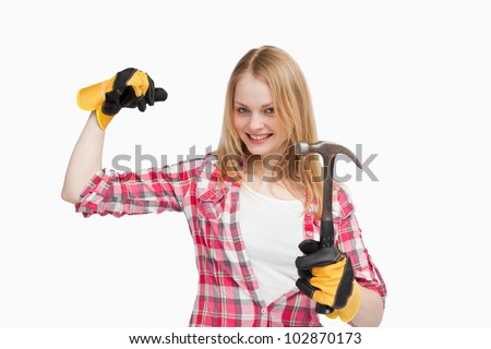 Joyful woman holding a hammer against white background - stock photo