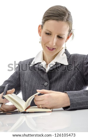 Joyful woman looking in her diary. Isolated over white background. - stock photo