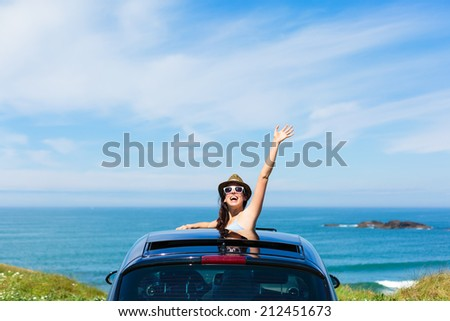 Joyful woman waving on summer car travel vacation to the coast. Brunette girl having fun leaning out vehicle sunroof towards the sea. - stock photo
