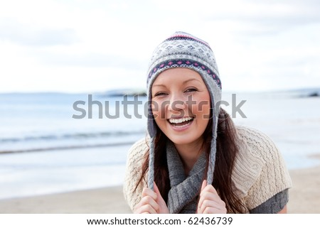 Joyful woman wearing hat and scarf on the beach - stock photo