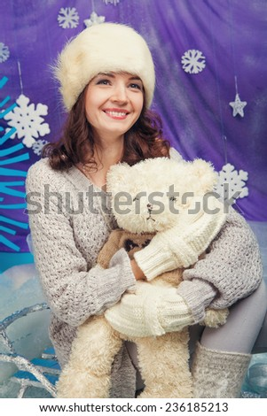 Joyful woman with teddy bears with xmas tree near by - stock photo