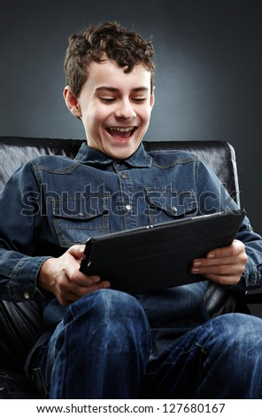 Joyful young boy sitting on leather chair, playing on tablet. Gray background - stock photo