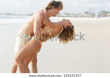 Joyful young couple being playful and romantic on a golden sand beach while on vacations. - stock photo