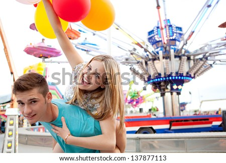 Joyful young couple being playful while visiting an attractions park arcade with rides, with young man giving girl a piggy bag and having fun. - stock photo