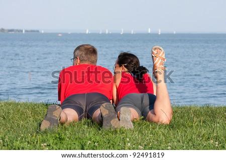 Joyful young couple is overlaping shore of the lake - stock photo