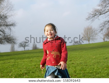 Joyful young girl child running down a green grass hill in a park with leafless trees and a blue sky during a sunny winter day, having fun and laughing outdoors. - stock photo