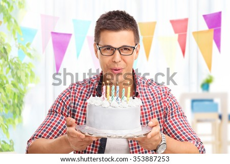 Joyful young man blowing candles on a birthday cake and looking at the camera at home - stock photo