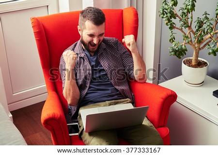 joyful young man screaming and looking at laptop - stock photo