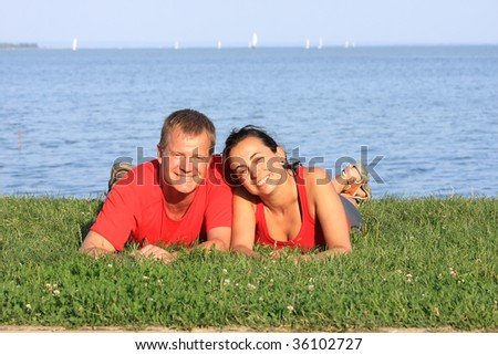 Joyful young pair is overlaping shore of the lake - stock photo