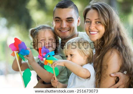 Joyful young parents holding kids with toy windmills at summer day  - stock photo