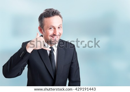 Joyful young salesman doing a call me gesture with hand as successful business concept with copyspace - stock photo