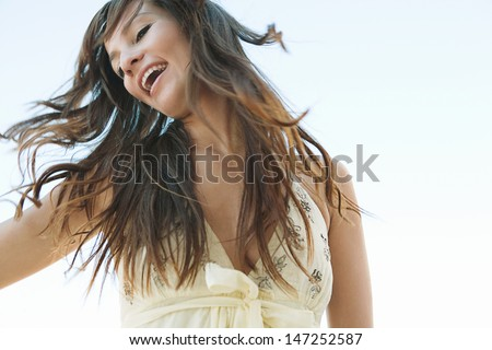 Joyful young woman flicking her hair in the air against a blue sky, smiling and feeling joyful and free and having fun during a sunny day. - stock photo
