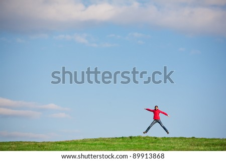 joyful young woman jumping in the middlle of a green field - stock photo
