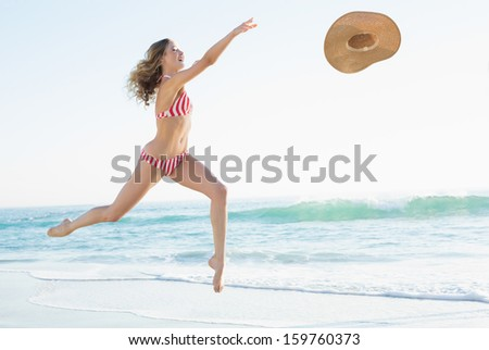 Joyful young woman jumping on beach trying to catch a straw hat - stock photo
