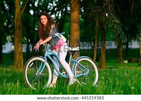 Joyful young woman on a bicycle in the green park at sunset - stock photo