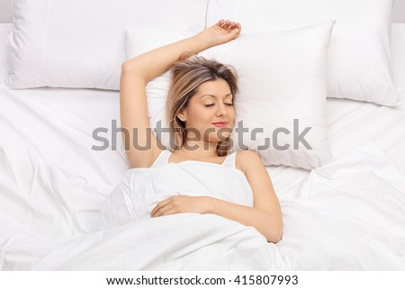 Joyful young woman sleeping on a comfortable bed and smiling  - stock photo