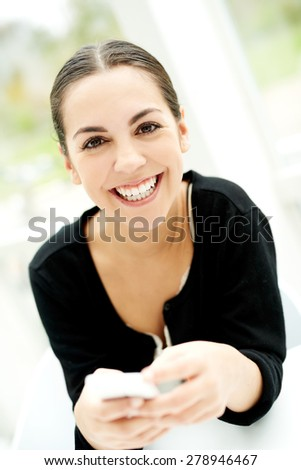 Joyful young woman smiling at the camera with a beaming smile as she sits holding her mobile phone in her hands - stock photo