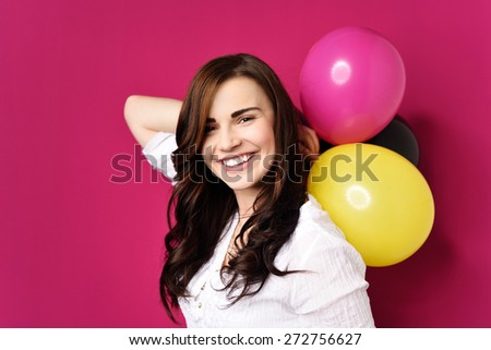 Joyful young woman with party balloons celebrating her birthday or a festive occasion beaming at the camera, over magenta - stock photo