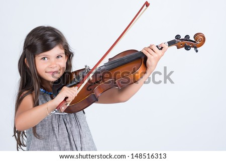Joyfull baby girl playing musical instrument on white background isolated - stock photo