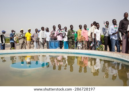 Juba, South Sudan - February 15, 2014: South Sudanese men wait in line to join a Sudan People Liberation Movement rally - stock photo