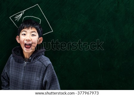 Jubilant Asian boy in classroom setting with graduate hat on chalkboard background and copy space. Concept for university education and future aspirations. - stock photo