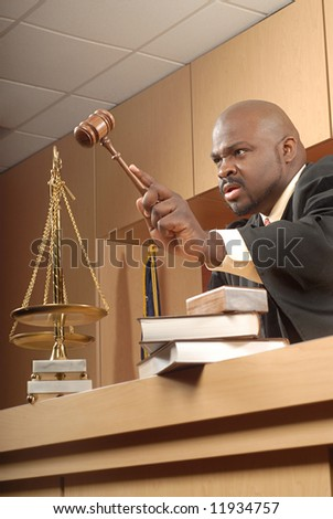 Judge banging his gavel and trying to bring the courtroom to order - stock photo