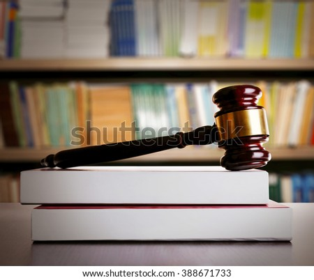 Judge gavel and books on wooden table on book shelves background - stock photo