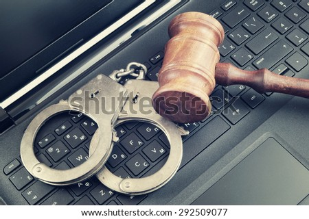 Judge gavel and handcuffs on laptop computer, cyber law or crime concept - stock photo