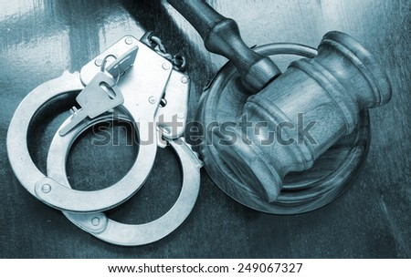 Judge gavel and handcuffs on wooden table, court concept - stock photo