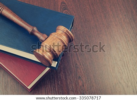 Judge gavel and legal books on wooden table - stock photo