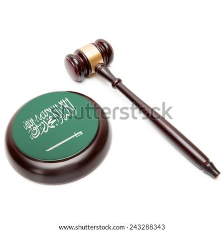 Judge gavel and soundboard with national flag on it - Saudi Arabia - stock photo