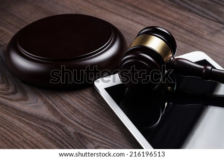 judge gavel and tablet computer on the table - stock photo