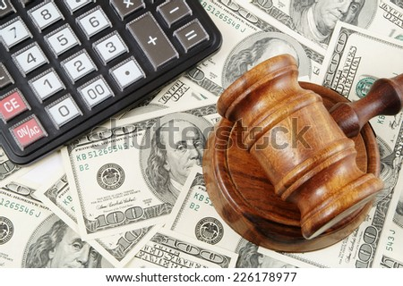Judge gavel, calculator and dollar banknotes  - stock photo