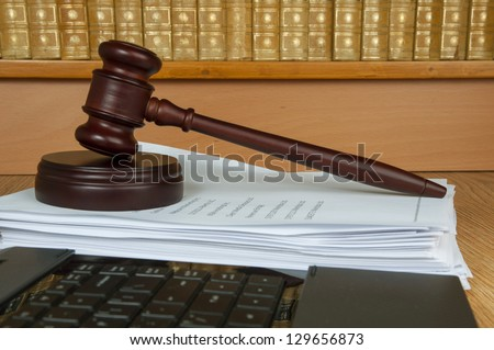Judge gavel with computer and old legal books in the background - stock photo